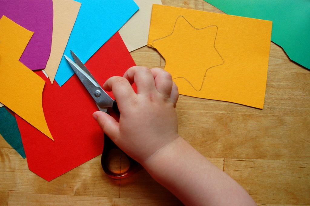 Ein Bild von einer Kinderhand mit einer Schere und Bastelmaterial
