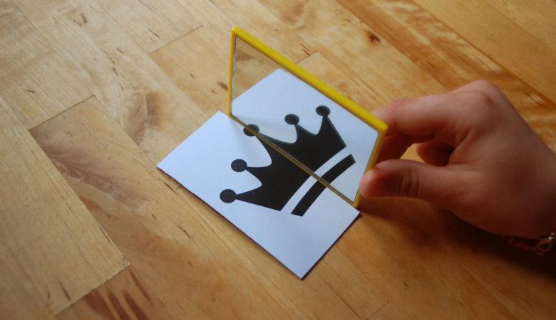 Foto von einem Kind, welches mit Hilfe eines Spiegels die Achsensymmetrie erforscht