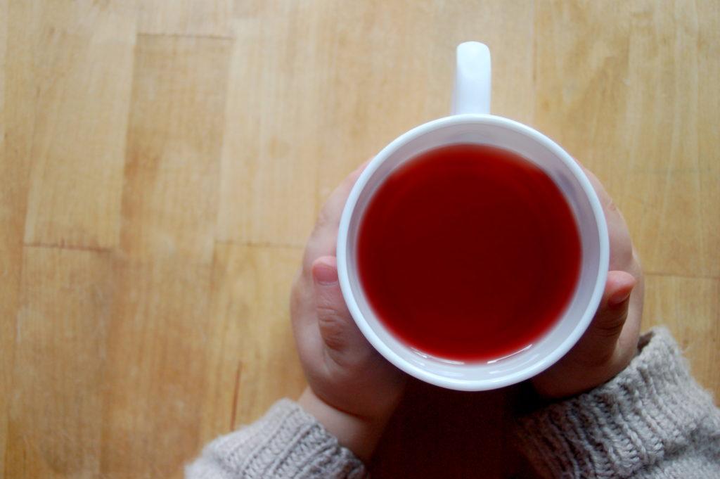 Foto von niedlichen kleinen Kinderhänden mit einer Tasse Tee