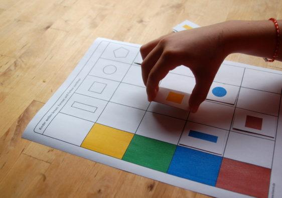 Foto von einem Kind, welches ein Lernspiel mit Farben und Formen spielt