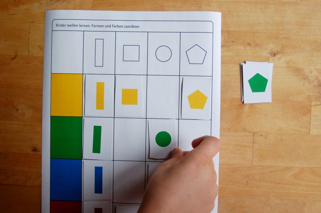 Foto von einem Kind, welches Farben und Formen zuordnet