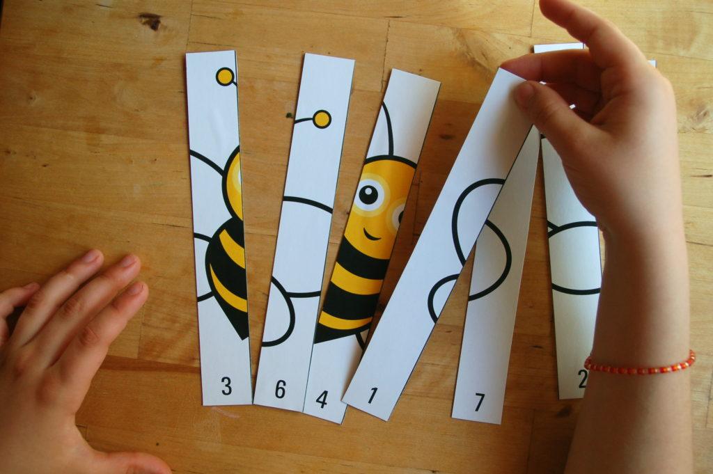 Foto von einem Kind, welches ein Zahlenpuzzle mit einer Biene zusammen setzt