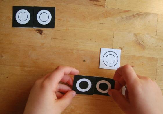 Foto von einem Kind, welches die Teile eines Zuordnungsspiels zusammen sortiert