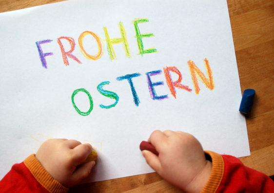 """Foto von Kinderhänden, die """"Frohe Ostern"""" aufgeschrieben haben"""