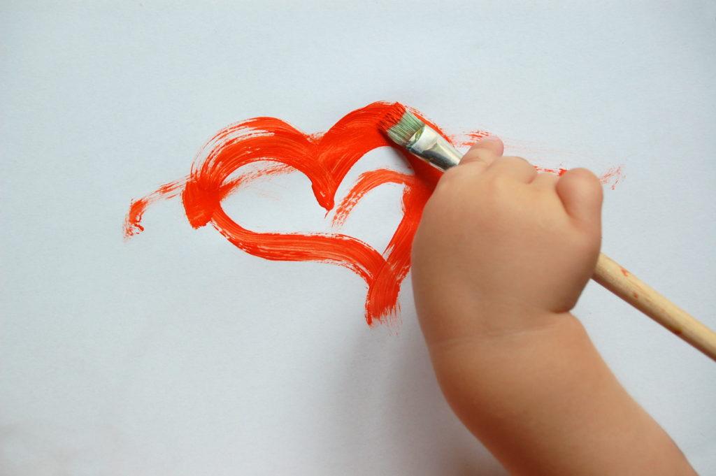 Foto von einer Kinderhand, die ein Herz malt, als Symbol für die freie Entfaltung, welche öffnetliche Lernorte versprechen