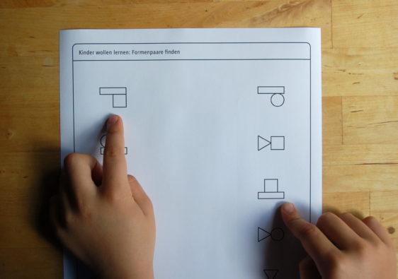 Foto von einem Kind, welches Formenpaare zuordnet