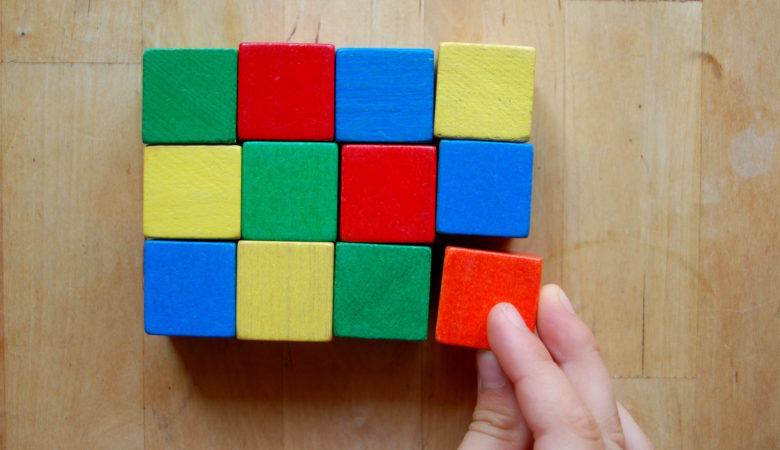 Foto von einem Kind, welches ein Muster aus Bauklötzen legt und damit eine erste Idee zum Thema Parkettierung erhält
