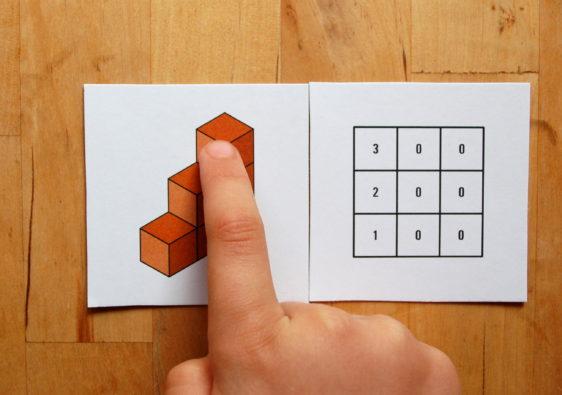 Foto von einem Kind, welches mit Hilfe eines Lernspiels Würfelgebäude versteht
