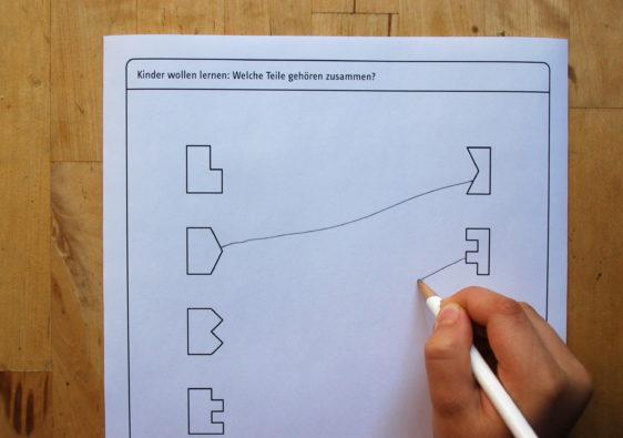 """Foto von einem Kind, welches das Arbeitsblatt mit dem Kinderrätsel """"welche Teile gehören zusammen?"""" löst"""