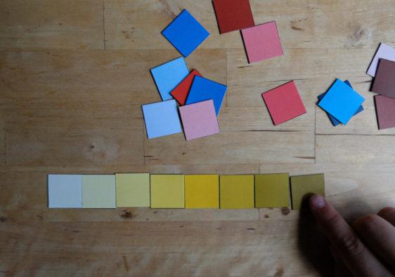 Foto von einem Kind, welches mit Farbkärtchen Farbabstufungen erforscht