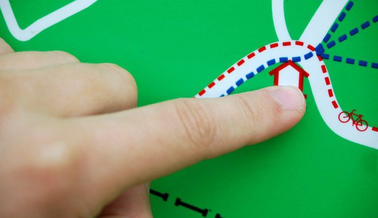 Foto von einem Finger, der auf ein Ziel auf einer Wanderkarte zeigt. Um zum Ziel zu kommen, muss man die Begriffe rechts und links unterscheiden können.