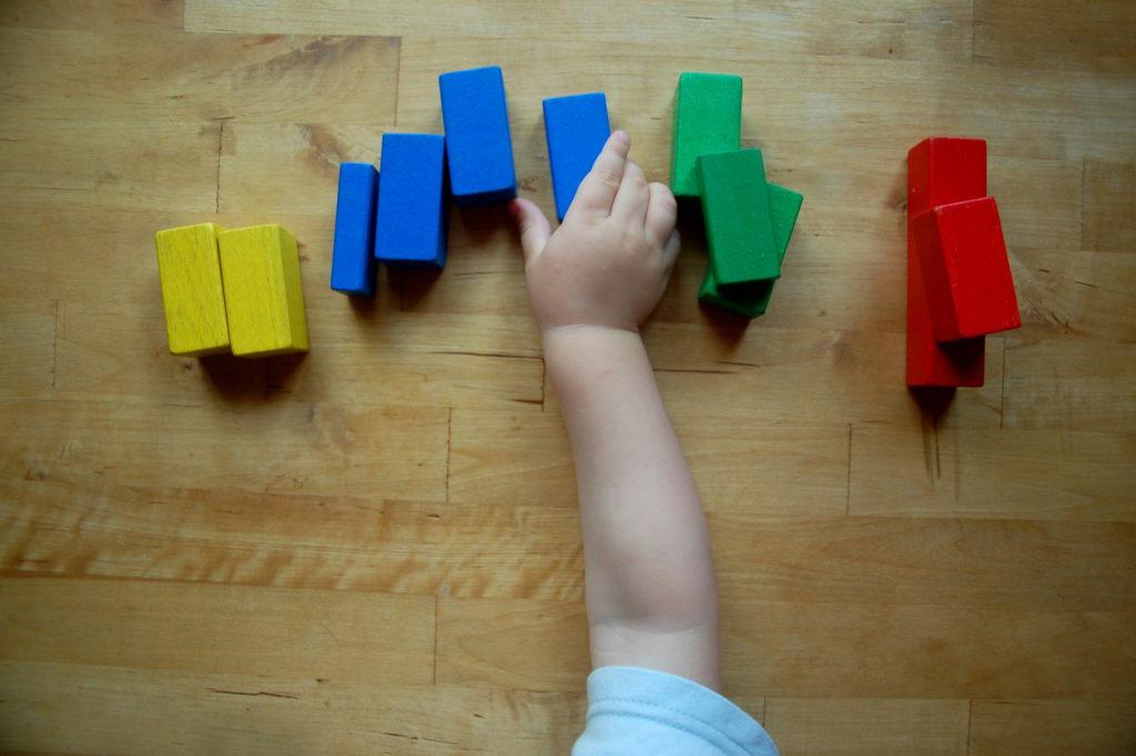 Foto von einem Kind, welches seine Bauklötze nach Farben sortiert