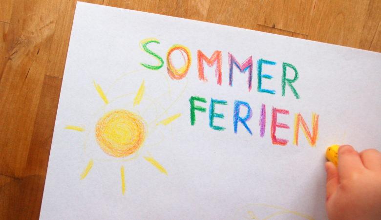 """Foto von einem Kind, welches eine Sonne malt und das Wort """"Sommerferien"""" dazu schreibt"""