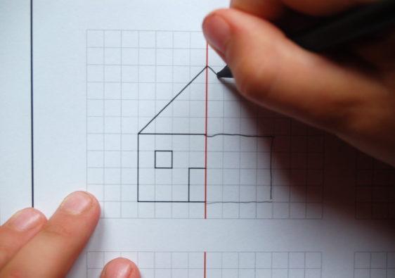 Foto von einem Kind, welches symmetrische Figuren vervollständigt und sich mit dem Thema Achsensymmetrie befasst