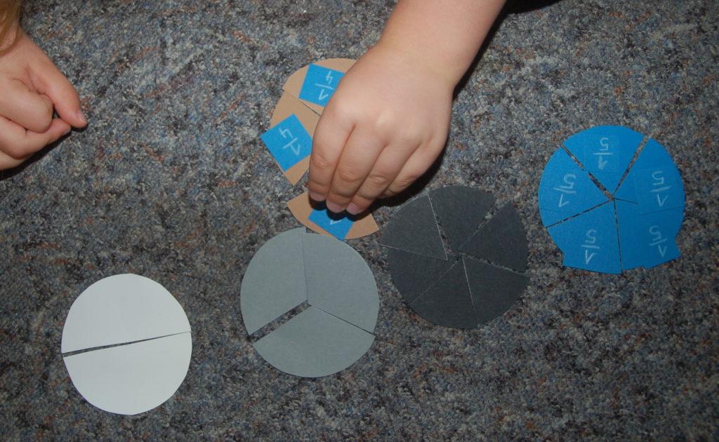 Einführung in die Bruchrechnung: Foto von einem Kind, welches sich mit Hilfe von Pappkreisen mit Brüchen vertraut macht