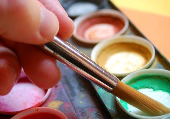 """Foto von einer Hand mit Pinsel und Wasserfarben passend zum Thema """"Farben mischen"""""""