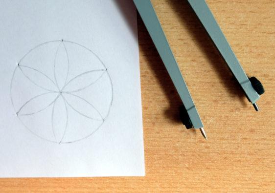 Foto von einem Zirkel und einer kleinen Zeichnung, die mit dem Zirkel entstanden ist